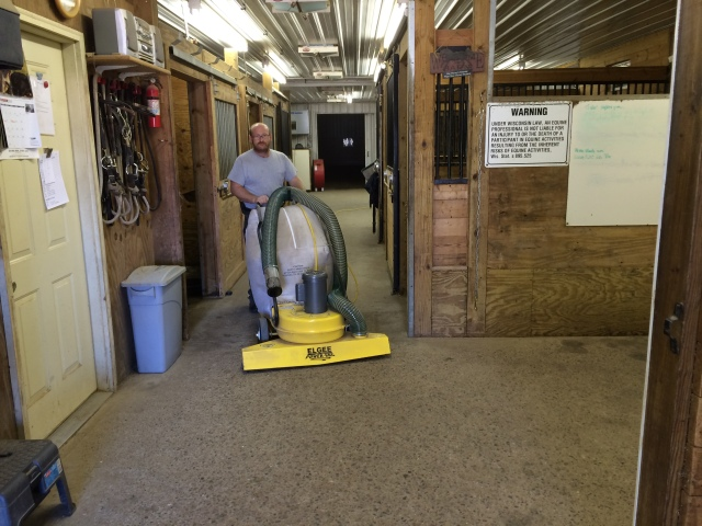 Bruce vacuuming the aisle in the main barn